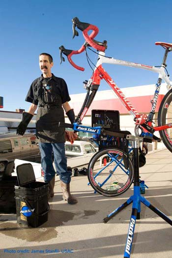 Calvin Jones in shop apron next to bike on repairstand outdoors