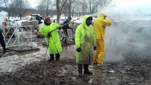 Three men in long bright coats using the power washer to wash up