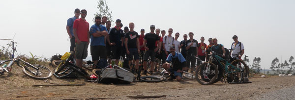 Group of cyclists posed behind small pile of bikes