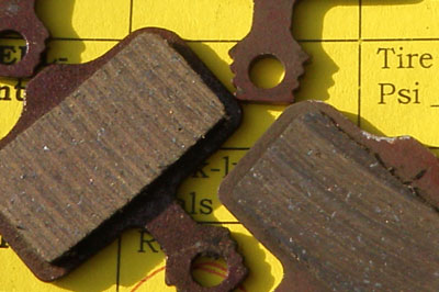 Old brake pad next to new brake pad