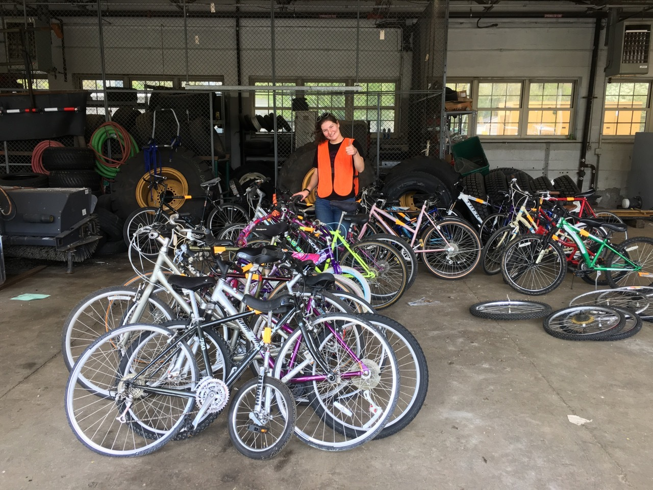 Volunteer giving a thumbs-up behind a row of bikes
