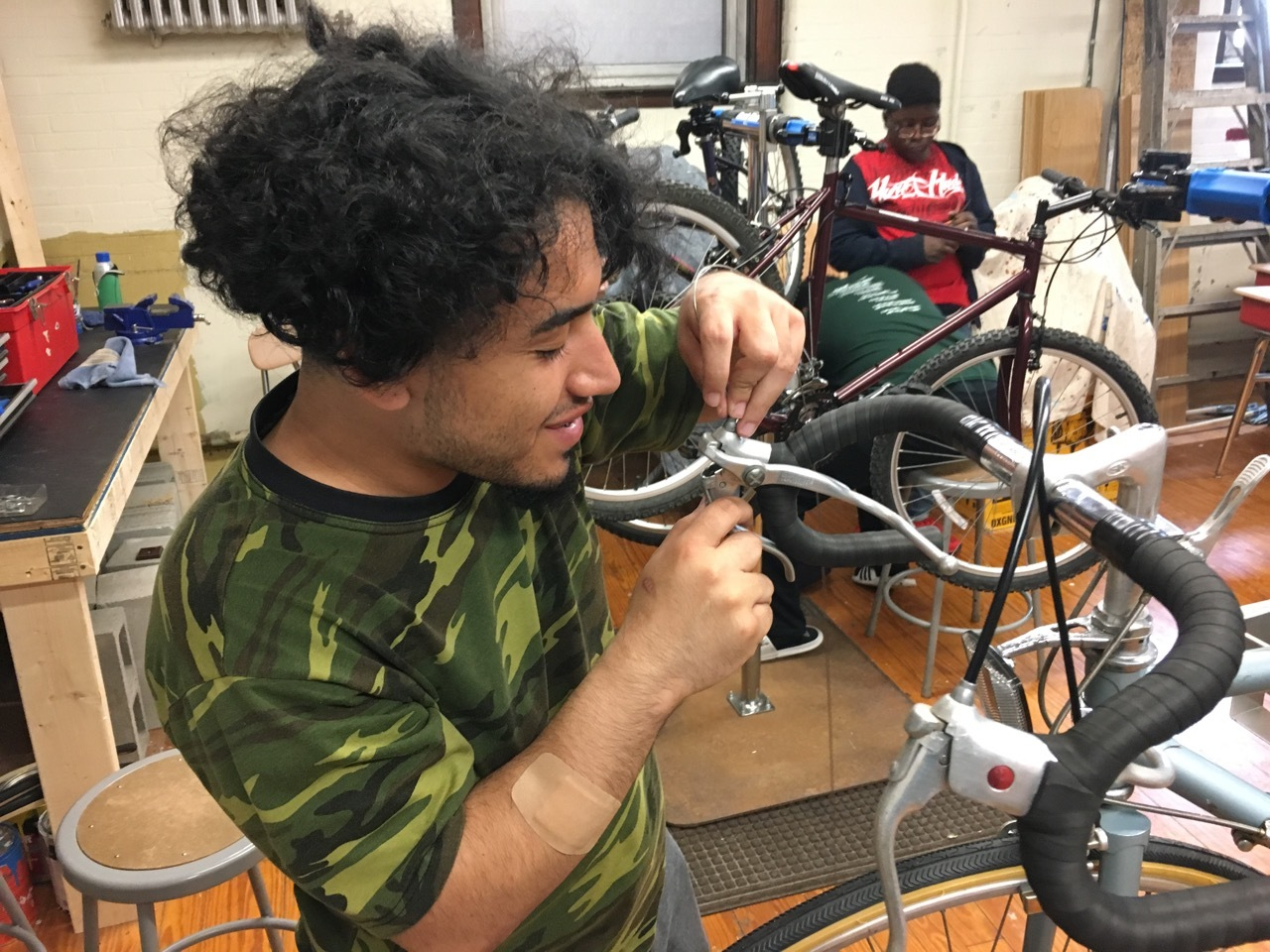 Two young people working on bikes in stands