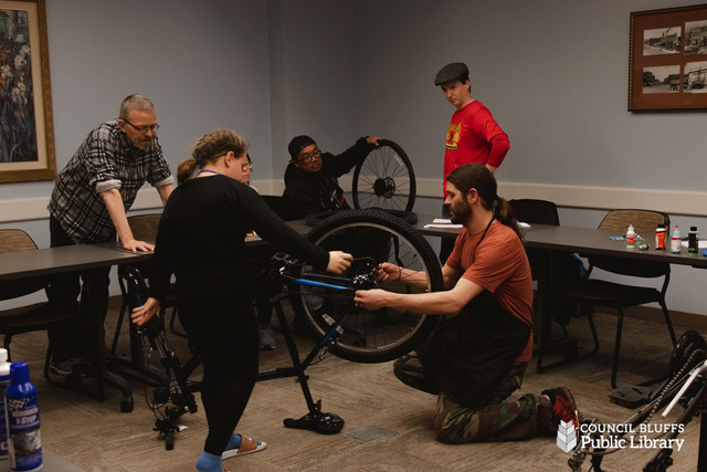 Adults and children working on bikes in classroom environment