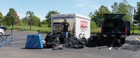 Large amount of bikes and equipment in front of truck and POD storage