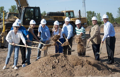 Large group of men and women with hardhats, shoveling a large pile of dirt