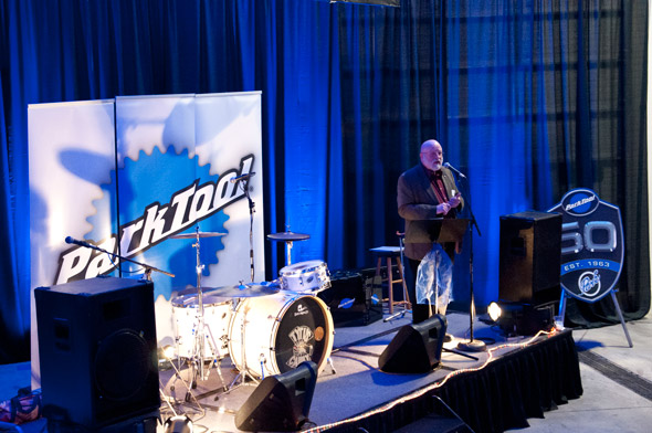 Stage with interments with large Park Tool logo behind and Jay Townley at microphone
