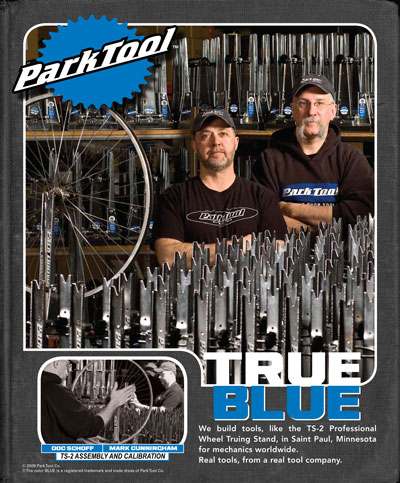 """Park Tool advertisement, two men posing in front of truing stands with text """"True Blue"""""""