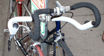 A bullhorn bar wrapped in white tape, and drop bars wrapped in black, with a randonneur bend.