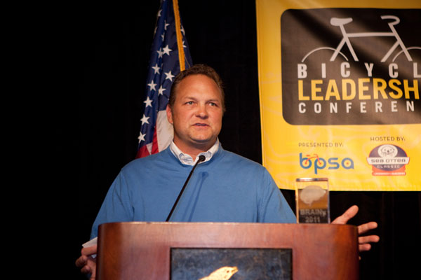 Eric Hawkins accepting award at podium at Bicycle leadership conference