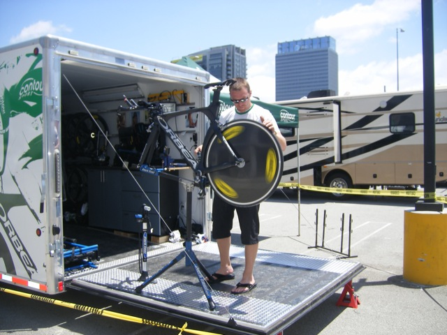 Eric Jellum on back of trailer working on bike mounted on Park Tool repair stand