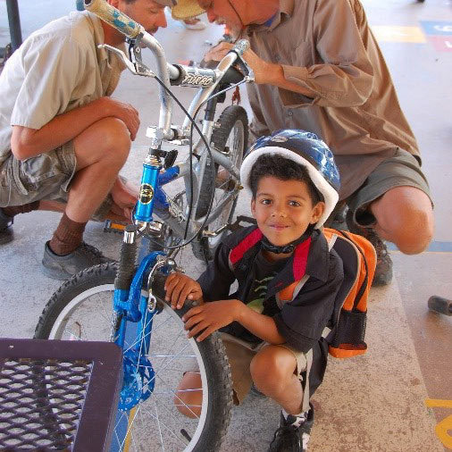 Child from Living Streets non profit posing next to bike