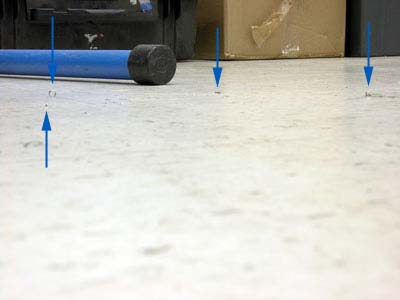 Parallel shot of white tiled floor, arrows pointing out clippings'