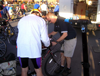 A technician finishes one bike while the Park Tool repair stand looks hungry for more work.