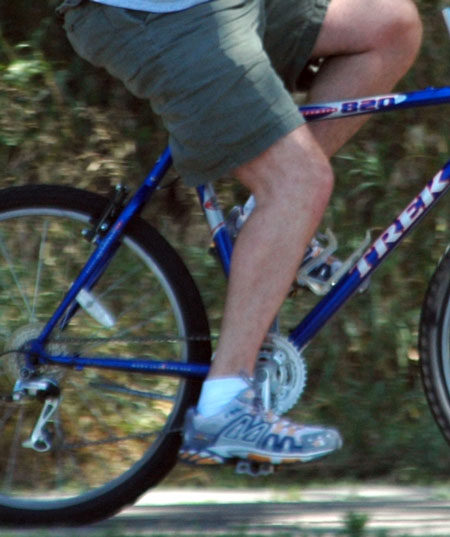 The foot here is very forward on the pedal. For this rider, move the foot back a bit, and raise the saddle.