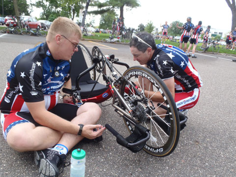 Andrew Chaffee (with Shimano support) on the right assisting in a hand cycle repair