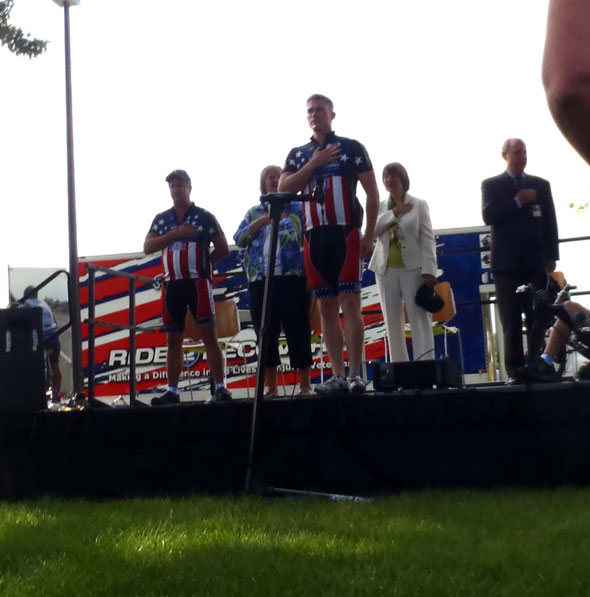 Four people on stage at bike event with hands on chest for pledge to flag