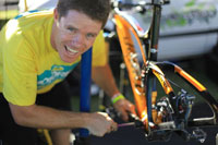 Rob Cunnington smiling at the camera while working on a bike