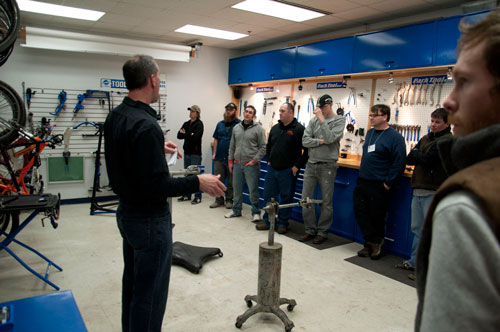 Dan Garecau speaking to a small group with the first prototype of the repair stand in front