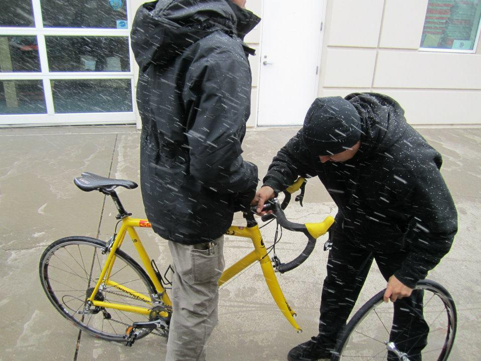 Two men in black jackets working on a yellow bike in the snow