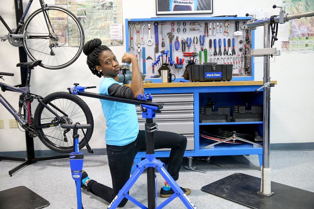 QBP womans scholarship participant posing in front of Park Tool workbench and repair stand