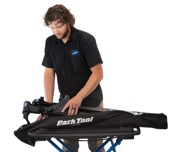 Park Tool tech guy Truman unpacking repair stand from the BAG-15 Travel and Storage Bag on portable workbench, click to enlarge