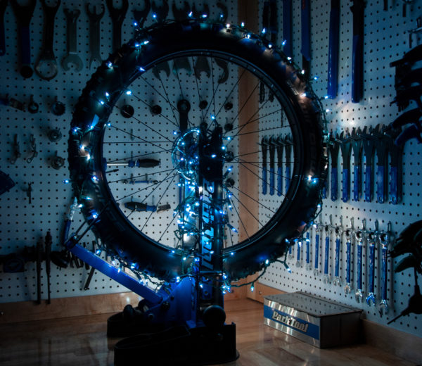 Bicycle wheel in a truing stand with blue Christmas lights wrapped around it in a workshop, click to enlarge