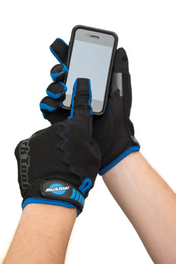 The Park Tool GLV-1 Mechanic's Gloves on hands holding smartphone and touching screen, click to enlarge
