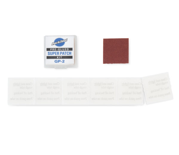 Pre-Glued Super Patch Kit contents (6 patches and small sandpaper) laid out, click to enlarge