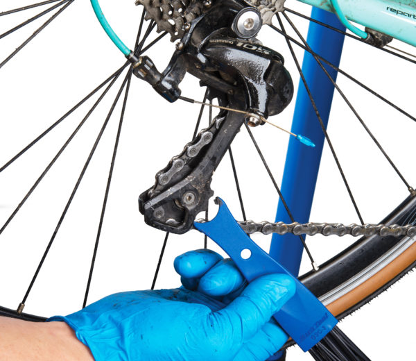 Contoured end of the Park Tool GSC-3 Drivetrain Cleaning Brush cleaning grit out from derailleur pulleys, click to enlarge