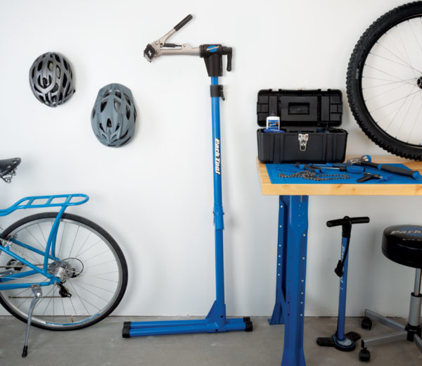 The Park Tool PCS-4-1 Deluxe Home Mechanic Repair Stand folded up, leaning against wall next to workbench, click to enlarge