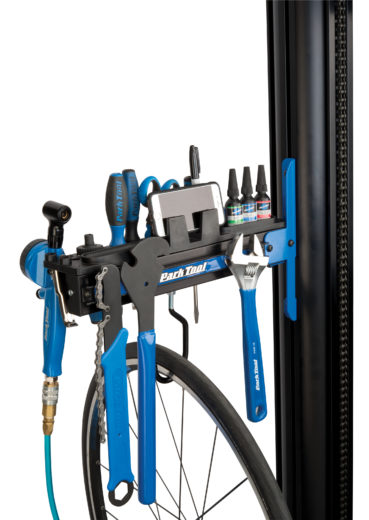The Park Tool PRS-33TT Deluxe Tool and Work Tray full of tools and a phone attached to repair stand, click to enlarge