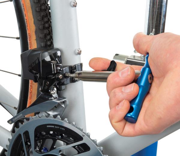 The Park Tool QTH-1 Quick Change Bit Driver Set handle driving a derailleur adjustment bolt, click to enlarge