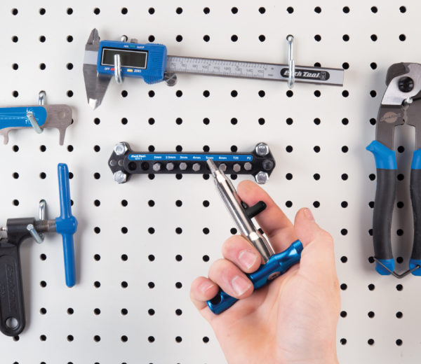 The Park Tool QTH-1 Quick Change Bit Driver Set handle returning a bit to holder mounted on pegboard, click to enlarge