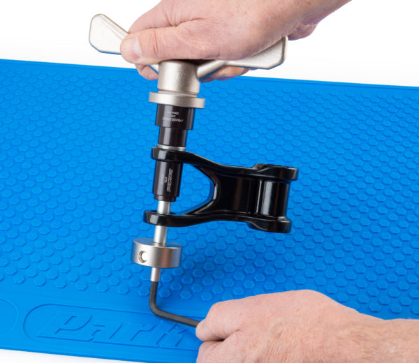 The Park Tool SBK-1 Suspension Bearing Kit installing new bearing into suspension linkage, click to enlarge