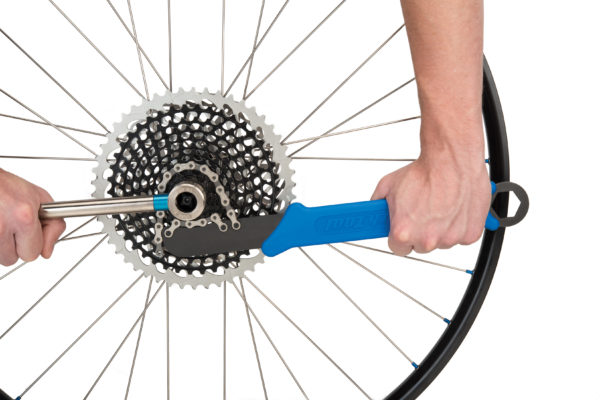 The Park Tool SR-12 Sprocket Remover / Chain Whip holding cassette while FR-5.2H loosens cassette lockring, click to enlarge