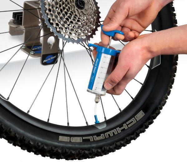 The Park Tool TSI-1 Tubeless Sealant Injector injecting sealant into Presta valve on MTB wheel, click to enlarge