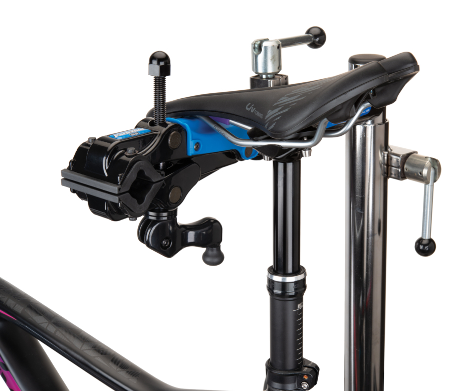 The Park Tool 100-3D Professional Micro-Adjust Clamp attached to stand with saddle resting on saddle cradle, enlarged