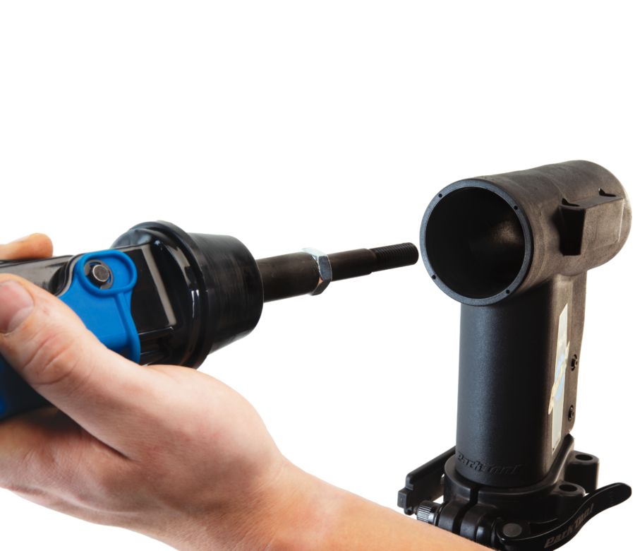 A Park Tool 100-25D micro-adjust clamp with 1951-15 adaptor stud being installed into PRS-15 repair stand, enlarged