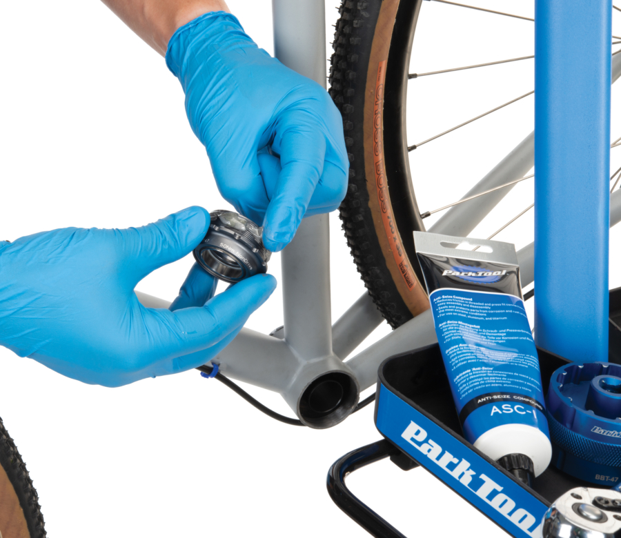 The Park Tool ASC-1 Anti-Seize Compound being applied to threads of bottom bracket cup, enlarged
