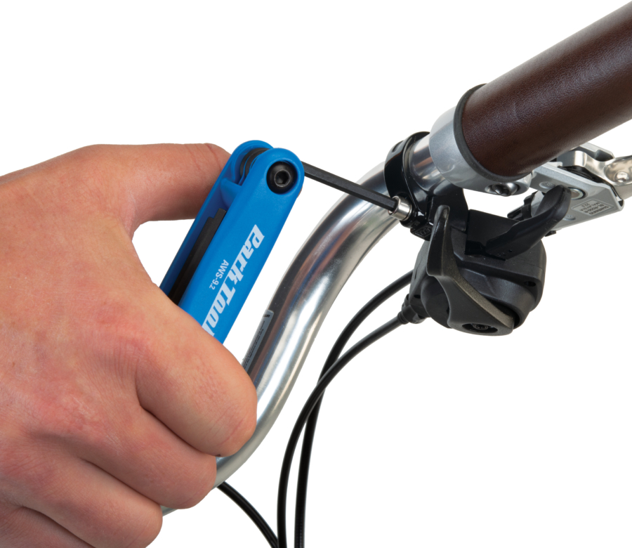 The Park Tool AWS-9.2 Fold-Up Hex Wrench Set securing a trigger shifter to handlebars, enlarged
