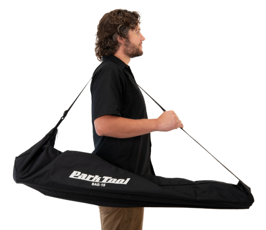 The Park Tool BAG-15 Travel and Storage Bag carrying repair stand, held by Park Tool tech guy Truman, enlarged