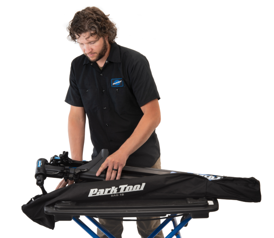 Park Tool tech guy Truman unpacking repair stand from the BAG-15 Travel and Storage Bag on portable workbench, enlarged