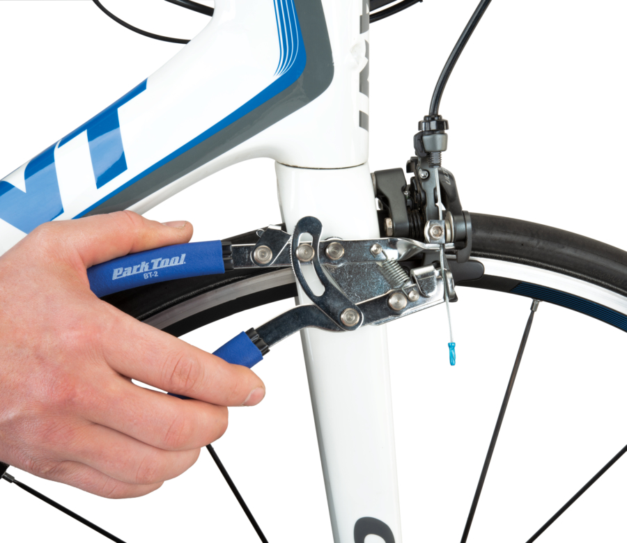 The Park Tool BT-2 Cable Stretcher holding front brake cable on road bike, enlarged