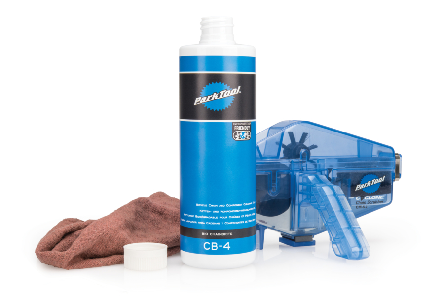 Bottle of Park Tool CB-4 Bio ChainBrite with a rag and CM-5.3 Cyclone™ Chain Scrubber, enlarged