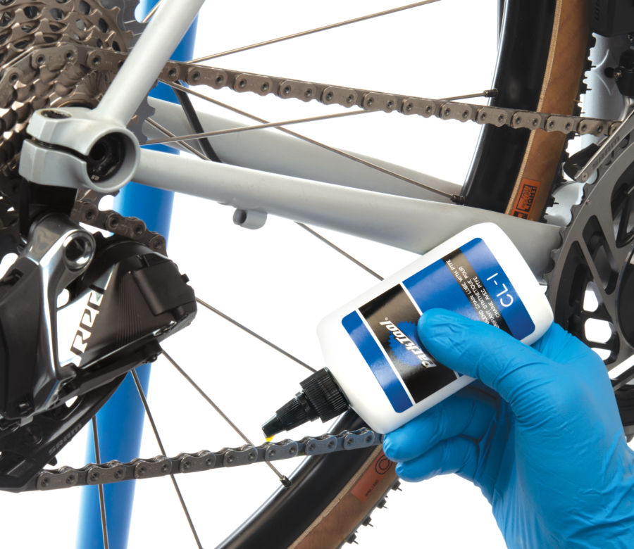 Park Tool CL-1 Synthetic Blend Chain Lube being used to lubricate SRAM® AXS® 12-speed chain, enlarged
