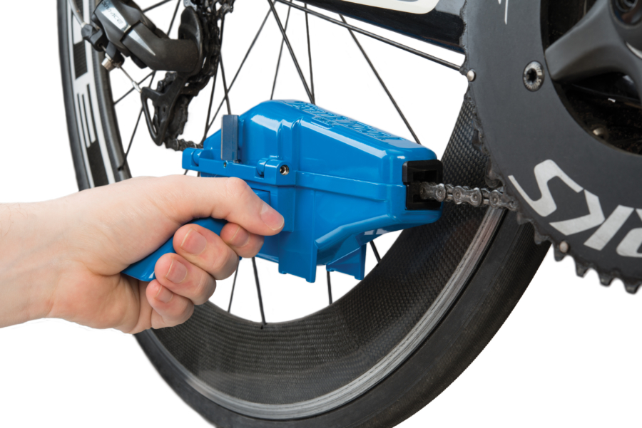 The Park Tool CM-25 Professional Chain Scrubber opened up installed on bicycle chain, enlarged