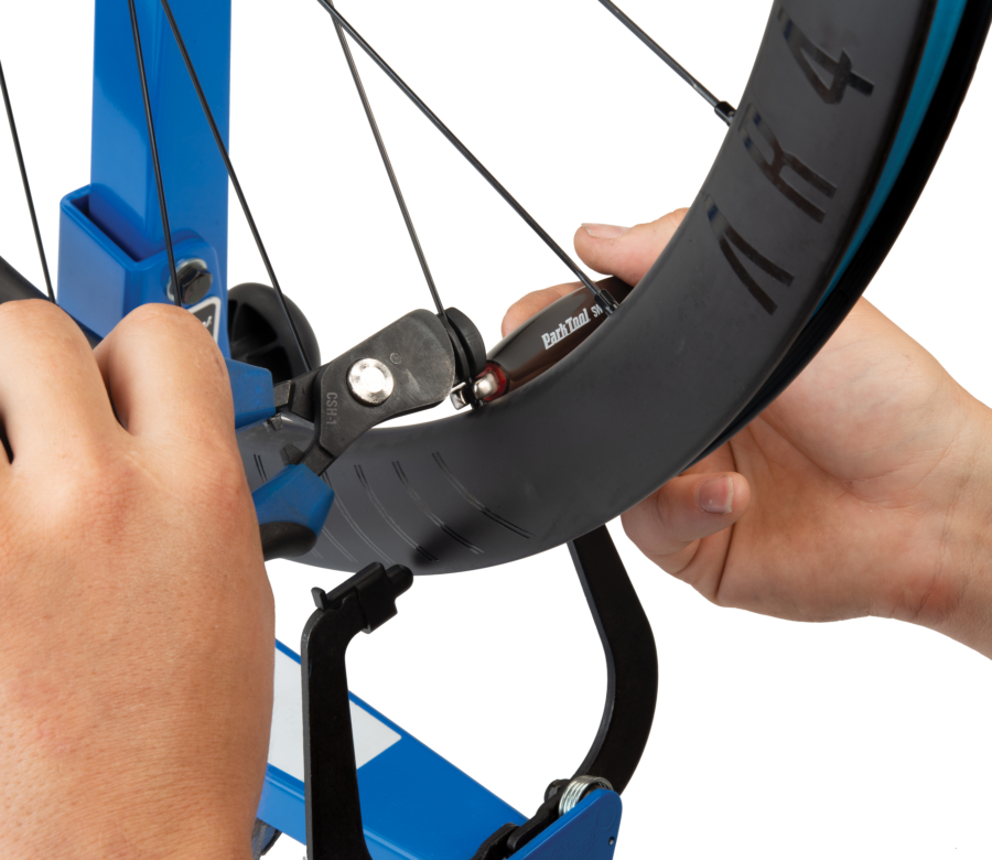 The Park Tool CSH-1 Clamping Spoke Holder holding a road wheel spoke while a wrench adjusts the spoke nipple, enlarged