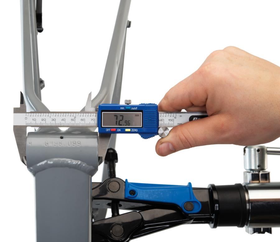 The Park Tool DC-1 Digital Caliper measuring the width of a threaded bottom bracket shell, enlarged