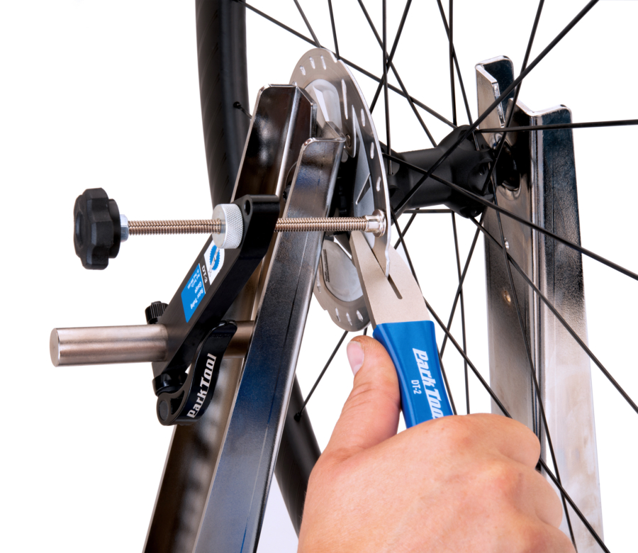 The Park Tool DT-3 Rotor Truing Gauge installed on a truing stand measuring disc rotor while rotor is trued, enlarged