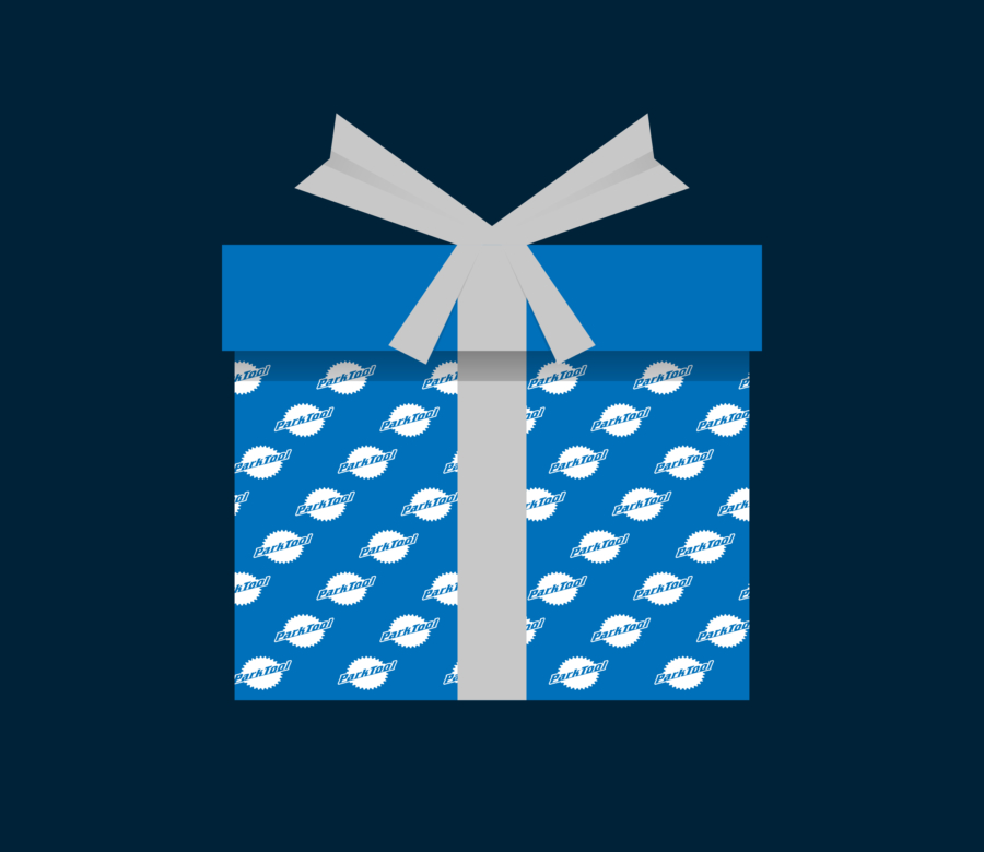 Illisdtration of a gift wrapped in blue Park Tool wrapping paper with a grey bow, enlarged